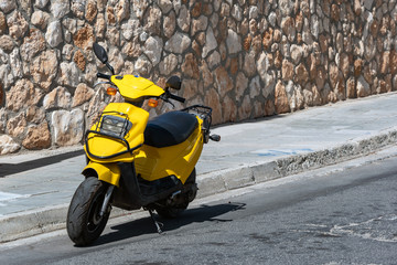 Picture of yellow moped or bike on the street