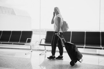 Travel business woman standing with luggage at airport.