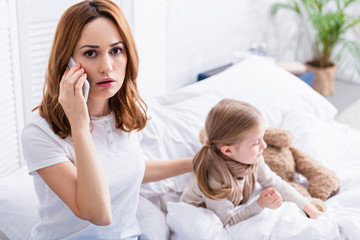 scared mother calling doctor by smartphone, sick daughter in bed