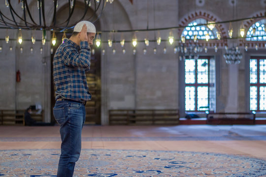 Young adult caucasian man praying and worship at the mosque