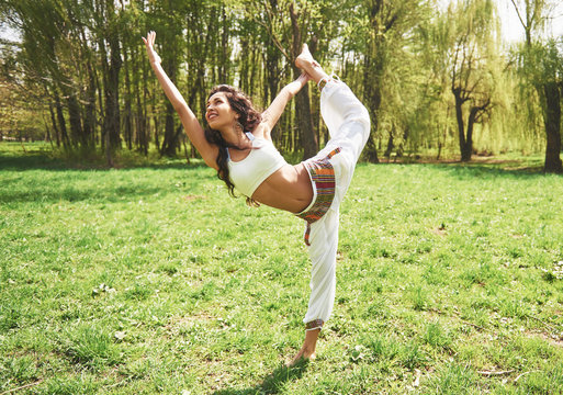 Practicing yoga of a beautiful girl in the morning on herbs under the sun's words.