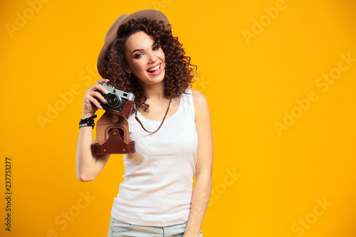 Portrait of laughing young woman taking pictures on retro