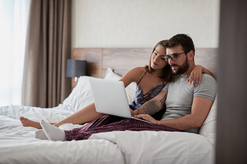 Young couple lying on bed at home and using laptop..