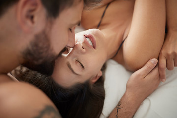 passionate kisses. Man with woman in bedroom. Top view.