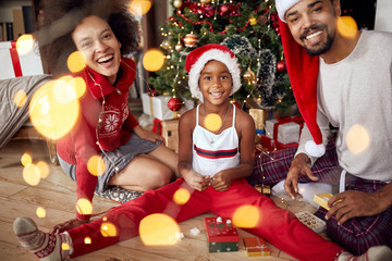 Portrait of family in front of Christmas tree.