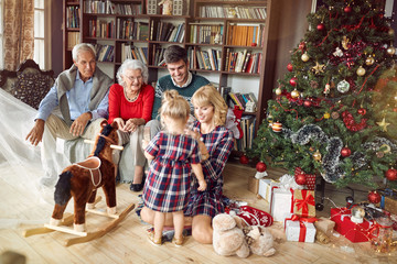 Cheerful parents with grandparents and little girl together for Christmas.
