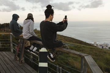 Skateboarders sitting on railing at observation point