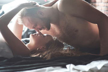 Attractive young lovers have couples playing together in bed, wearing sexy lingerie in a hotel room.