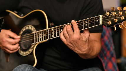 Closeup of a musician playing the guitar live at a greek restaurant