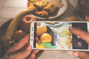 Smartphone in the hands of women, food photography, dinner on the table. apples, bananas, cookies