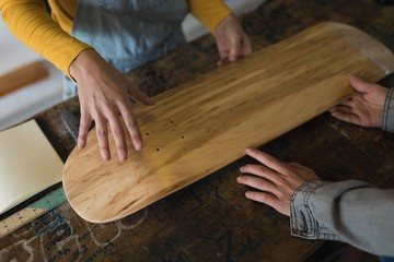 Skateboarders examining skateboard deck in workshop