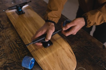 Man repairing skateboard in workshop