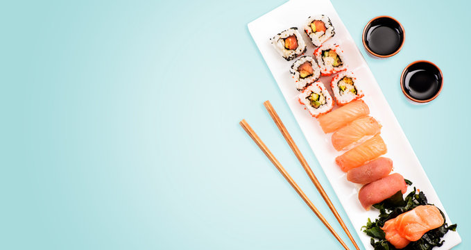 Sushi rolls set with salmon and tuna fish on light blue background from above.