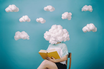 Woman reading book with head in cloud