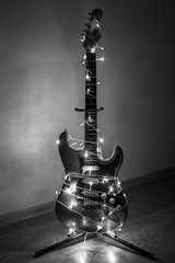 Electric guitar wrapped in colorful garland, the idea of holiday music, black and white photo