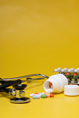 drugs and stethoscope on a yellow background