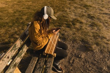 Woman listening music on mobile phone on the beach