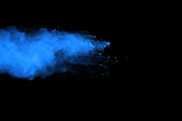 Freeze motion of blue powder explosions isolated on black background.