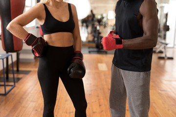 Male trainer assisting female boxer in fitness studio