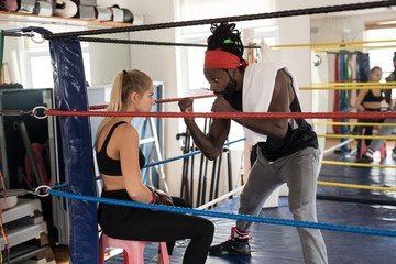Male trainer assisting female boxer in boxing ring