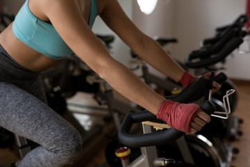 Female boxer exercising on exercise bike in fitness studio