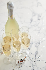 Champagne glasses and bottle placed on white marble background. Party and holiday celebration concept with confetti and serpentines. With copy space.