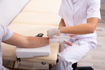Doctor Tying Bandage On Man's Hand