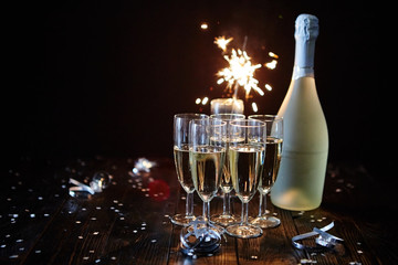 Party composition image. Glasses filled with champagne placed on black table. With bottle of wine and sparkler. Elegant composition with copy space.