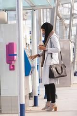 Hijab woman using ticket vending machine at railway station