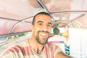 Man taking a selfie and having fun on a tuk tuk run in Bangkok