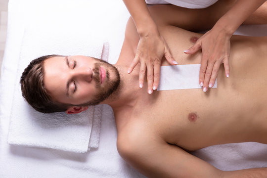 Beautician Waxing Man's Chest With Wax Strip