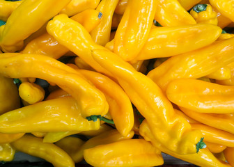 Display oblong yellow peppers in a supermarket
