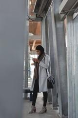 Woman using mobile phone in platform