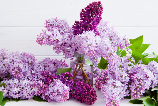 Purple flowers of lilac with leaves in a glass bottle on a white wooden background