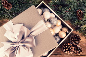 Christmas bauble decoration in a gift box with ribbon and bow. Flat lay. Wooden background.