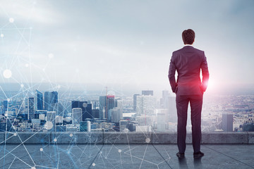 Businessman looking at city, network Wall mural
