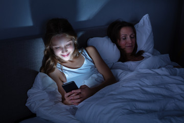 Girl Using Mobile Phone While Her Daughter Sleeping On Bed