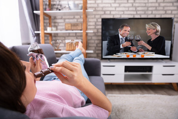 Woman Eating Chocolate While Watching Television