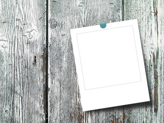 Blank square instant photo frame on white weathered wooden boards background