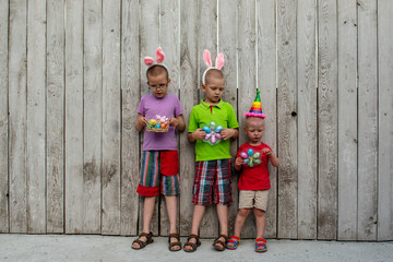 Funny children in carnival hats stand in colorful costumes in front of wooden fence in rural yard. Brothers are happy together. Tradition of family holidays