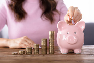 Woman Inserting Coin In Piggybank