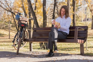 Man having coffee while sitting on a bench in the park