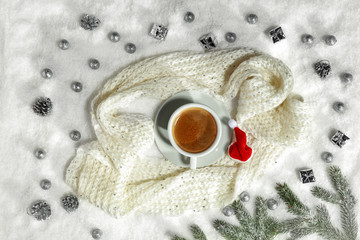 Hot coffee on the snow with a woolen scarf on a festive evening