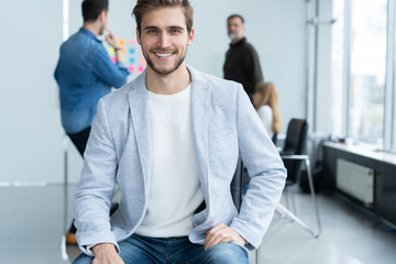 Enjoying his work. Handsome young man looking at camera and smiling while his colleagues working in the background.