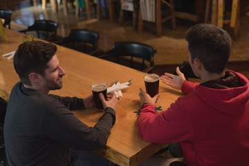 Friends talking with each other while having beer at counter