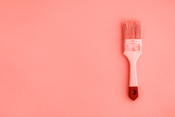 Painting brush on living coral color background.