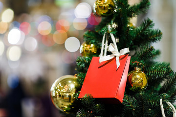 Photo of Christmas fir with gold balls, red packet for gifts .