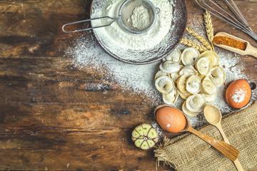 Italian ravioli, dumplings with meat and ingredients on dark wooden old surface