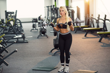 Athletic young woman doing biceps exercise with barbell in the gym. Sporty and healthy concept.