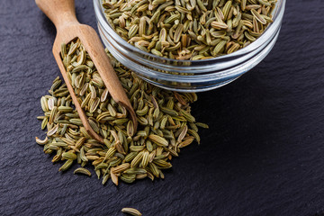 Essential oil of fennel seeds on a dark stone background